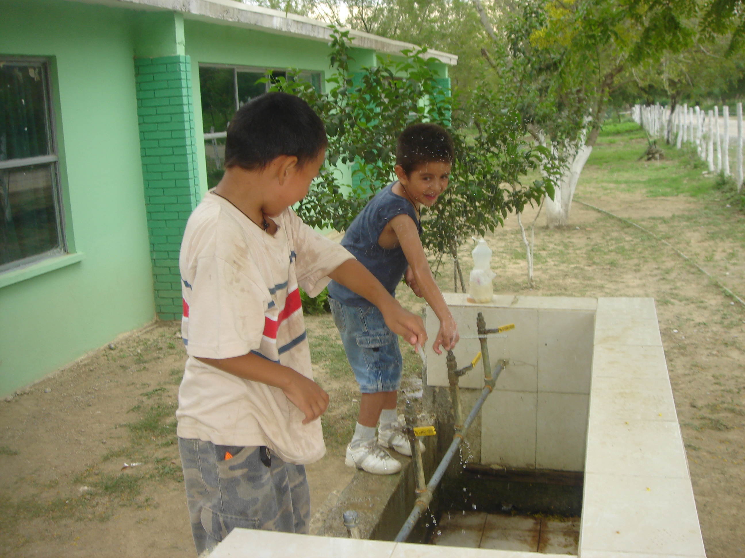 Mexican children playing in the drinking fountain at their school
